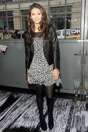 Nina Dobrev topped off her look with black tights and black suede ankle boots.