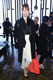 Elettra Wiedemann oozed classic style in a black wool coat teamed with white slacks at the DKNY fashion show.
