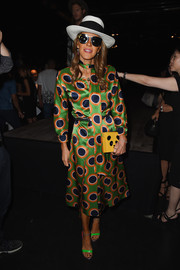 Anna dello Russo completed her fanciful ensemble with a yellow panda box clutch by Charlotte Olympia.