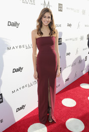 Kaia Gerber put her svelte figure on display in a fitted burgundy strapless gown by Solace London at the Fashion Los Angeles Awards.