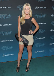 Tinsley paired her khaki shorts and black tank top with a studded leather clutch.