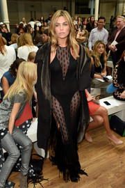 Abbey Clancy sizzled in a fringed black sheer-panel dress by Julien Macdonald during the brand's fashion show.
