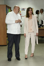 Queen Letizia of Spain donned a slouchy pink pantsuit and a matching silk blouse for her tour of Port-au-Prince, Haiti.