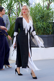 Chloe Sevigny teamed a black duster with a white eyelet blouse and skirt, all by Loewe, for the 2019 Cannes Film Festival photocall for 'The Dead Don't Die.'