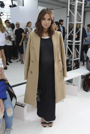 Miroslava Duma layered a basic beige wool coat over a black maxi dress for the Delpozo fashion show.