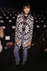 Langley Fox attended the Desigual fashion show wearing a festive print coat over a sheer-panel bodysuit.