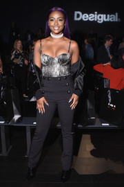 Justine Skye paired her sexy top with black side-striped slacks.