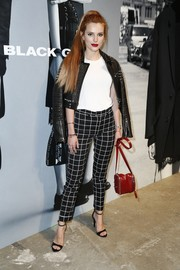 Bella Thorne accessorized with a red Diesel bag for a splash of color to her monochrome outfit.