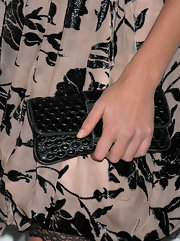 Charlize Theron accented her flower print dress with a textured scaled black leather clutch.