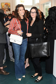 Gina Gershon attended the Director's Circle party carrying a classic quilted leather bag by Chanel.