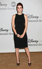 The actress wore a black sheath dress with patent panels on the waistline.