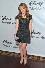 Lea Thompson paired her flirty dotted dress with an unexpected beaded skull clutch.