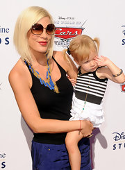 Tori toted her adorable tot while sporting a sleek bob with round gold shades.