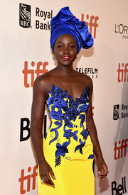 Lupita Nyong'o paired an electric-blue headdress with a strapless gown (both by Carolina Herrera) for the TIFF screening of 'Queen of Katwe.'