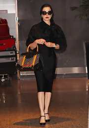Dita Von Teese traveled in style in a chic all-black ensemble topped off with patent leather black Mary Jane pumps.