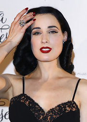Dita Von Teese's signature red stiletto nails involve working a nail file back and forth from one corner of the nail in an upward motion toward the center. Then the process is repeated on the other side, making sure never to saw back and forth across the entire nail. For color options, OPI Nail Color in And a Cherry On Top or Sally Hansen Nail Color in Red Hot work beautifully for creating a similar style.