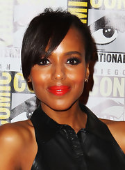 Kerry Washington painted her lips a bright orange-red to go with her floral skirt.