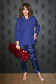 Oh how sweet it is! Paola Maugeri brightened up her purple pantsuit with a red clutch in the shape of ginormous candy bar.