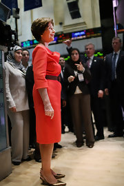 Laura Bush brought a bright pop of color to the New York Stock Exchange in an orange cowl-neck dress.