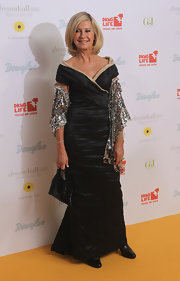 Olivia Newton-John donned a sophisticated off black off the shoulder gown. She added sparkle with a glittering shawl.