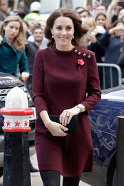 Kate Middleton paired a black Mulberry suede clutch with a maroon mini dress for the Place2Be School Leaders Forum.