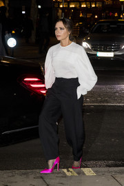 Victoria Beckham added a pop of color with a pair of hot-pink satin pumps.