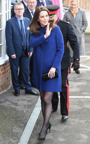 Kate Middleton paired her coat with an elegant croc envelope clutch by Aspinal x Beulah.