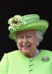 Queen Elizabeth completed her accessories with a pair of pearl studs and a matching necklace.