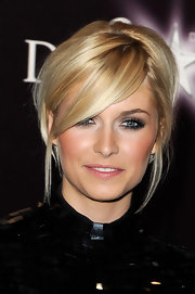 Lena keeps her updo modern with side-swept long bangs and a few loose tendrils.
