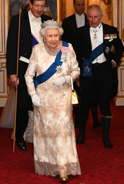 Queen Elizabeth II looked elegant in a white and gold lace column dress while attending a reception for members of the Diplomatic Corps.