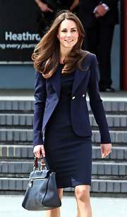 Kate Middleton accented her posh travel attire with a pebbled navy blue leather Polly Push-lock bag.