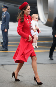 Kate Middleton showed off her classic style in a red Catherine Walker coat adorned with two rows of silver buttons as she landed in New Zealand.
