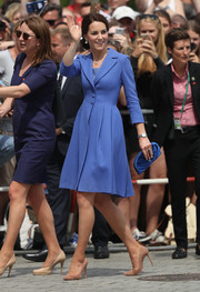 Kate Middleton polished off her look with a ruched blue satin clutch by Jimmy Choo.