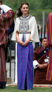 Kate Middleton paired her cape with a vibrant-hued wrap skirt.