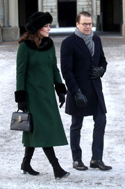 Kate Middleton took a stroll in Stockholm wearing a forest-green coat by Catherine Walker, which she accessorized with a black faux-fur collar and cuffs.