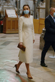 Kate Middleton looked perfectly refined in a cream-colored Catherine Walker wool coat with a lace-embellished front while visiting a Covid-19 vaccination center.