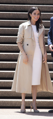 Meghan Markle stopped by the Sydney Opera House wearing a classic trenchcoat by Martin Grant over a white midi dress.