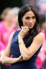 Meghan Markle paired an elegant gold bangle by Shaune Leane with a navy dress for a reception in Melbourne, Australia.