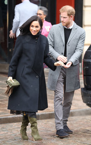 Meghan Markle completed her winter-chic look with olive-green knee-high boots by Sarah Flint.