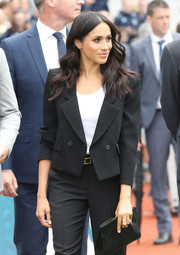 Meghan Markle teamed a black leather clutch with a pantsuit, all by Givenchy, for her visit to Croke Park in Ireland.