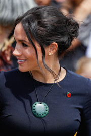 Meghan Markle accessorized with an oversized Maori greenstone pendant.