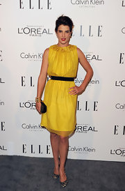 Cobie Smulders toughened her marigold frock with a black hard case clutch with studded details.