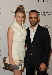 Chloe Moretz modernized her white shirtdress with a sleek cream clutch with a pewter hand strap.