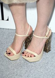 Emilia Clarke rocked a chunky pair of nude platform sandals with sculpted gold heels during the Elle Women in Hollywood celebration.