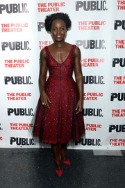 Lupita Nyong'o was prom-glam at the opening of 'Eclipsed' in a sequined red fit-and-flare dress by Christian Dior.
