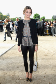 Olivia Palermo attended the Elie Saab fashion show wearing camo-print pumps, leather pants, a fitted jacket, and a patterned blouse.