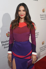 Olivia Munn attended the Time for Heroes Family Festival carrying a metallic purple clutch by Edie Parker.