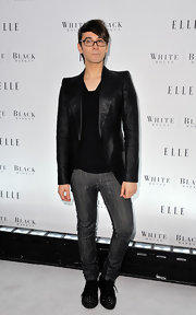 Christian wears a shiny black blazer with a slim fit and pointed shoulder design.