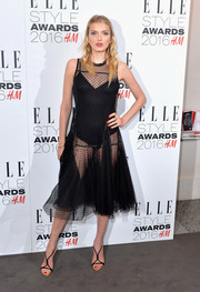 Lily Donaldson continued the sultry vibe with a pair of black T-strap sandals.