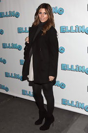 Jamie-Lynn wears a classic black wool pea coat over tights and black booties.